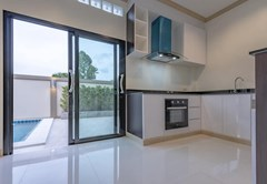 House for sale Pattaya Mabprachan showing the kitchen and sliding door to swimming pool